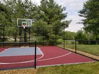 View of red and grey backyard basketball court in Groton, MA.