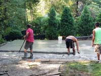 Workers shaping and smoothing cement for base of residential basketball court in shades of blue in Lexington, MA.