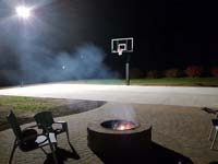 Preview of incomplete basketball court featuring Celtics logo, with fire pit, patio, and light for night play, in Londonderry, NH.