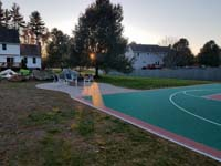 Basketball court featuring Celtics logo, with fire pit, patio, and light for night play, in Londonderry, NH.