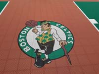 Closeup of logo on a basketball court featuring Celtics logo, with fire pit, patio, and light for night play, in Londonderry, NH.