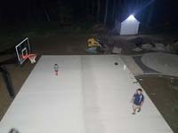 Partially complete basketball court featuring Celtics logo, with fire pit, patio, and light for night play, in Londonderry, NH.