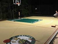 Kids checking out new backyard basketball court under the lights in Londonderry, NH, featuring custom logos and text on a tan and green sport surface