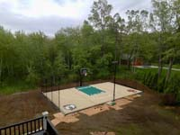 Overview of sand and green backyard basketball court in Londonderry, NH, featuring custom logos and text, optional net for additional court sports like tennis or volleyball, optional lighting for night play, and rebound fence.