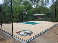View from a near angle of overall sand and green basketball court, highlighting the optional net that makes it a multiple sport court, also featuring custom text and team logos, in Londonderry, New Hampshire.