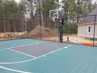 Green and black basketball court in Marion, MA, shown before completion of surrounding landscaping and pool.
