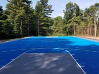 Large royal blue and titanium basketball court with golf seahorse logo at Bay Club in Mattapoisett, MA, as viewed from beneath hoop at one end, looking at the opposite end, showing the sheer size..