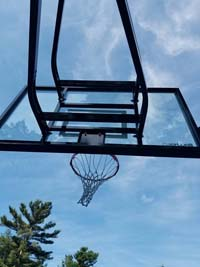 View of goal from below against sky at large royal blue and titanium basketball court with golf seahorse logo at Bay Club in Mattapoisett, MA.