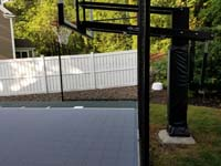 Side view of goal system and end of slate green and titanium silver/grey basketball court in Needham, MA.