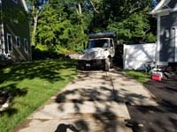 Driveway and part of front yard, showing protective measures taken during construction of slate green and titanium silver/grey basketball court in Needham, MA. Front view of dump truck shown above being loaded with grass and topsoil.