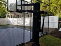 Rear view of goal system installed with slate green and titanium silver/grey basketball court in Needham, MA.