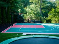Large green and red (that in some pictures looks orange) basketball court with in-ground trampoline shown in foreground, installed in Pembroke, MA. The customer opted for lighting for night play, plus lines and a net for additional sports like tennis and volleyball, making it a super functional multicourt.