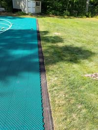 Edge of almost finished emerald green and royal blue basketball court over asphalt in Rehoboth, MA.