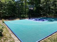 Emerald green and navy blue Versacourt basketball tile on blacktop court in Rehoboth, MA.