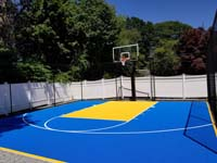 Stunning blue and yellow backyard basketball court in Stoneham, MA. Installing this included extensive drainage and landscape adjustments.