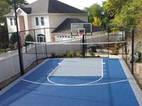 Blue and grey basketball court with optional net for other sports, making creative use of awkward yard space in Stoneham, MA.