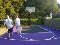 Catchy purple and black residential basketball court in Stoneham, MA takes advantage of a small, unused space in the yard.