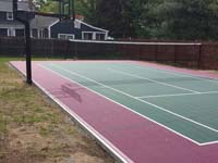 Backyard basketball and tennis multiple sport court in Sudbury, MA, surfaced with low impact, high performance burgundy and slate green outdoor Versacourt tiles.