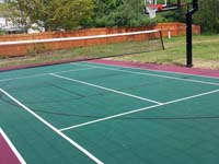 Backyard basketball court in Sudbury, MA, made to use for tennis and volleyball, giving more bang for the court purchase buck.