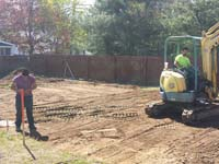Digging up grass and ensuring an underlay free of organic matter before creating a foundation for a backyard basketball court in Sudbury, MA.