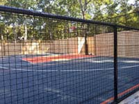 View through mesh fence at graphite and orange backyard basketball court with custom fence that incorporates more traditional wood in Walpole, MA.