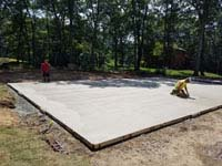 Smoothing cement underlay for graphite and orange residential basketball court replacing a dead pool in Walpole, MA.