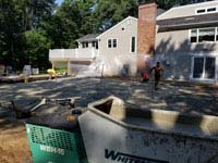 Installing concrete base for graphite and orange residential basketball court replacing a dead pool in Walpole, MA.
