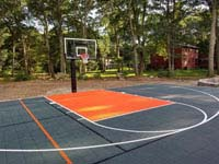 Graphite and orange backyard court in Walpole, MA, built over a filled in swimming pool. Subsequently a combination of cedar and custom containment fence was installed around it.