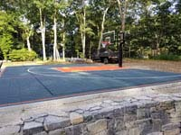 Graphite and orange backyard basketball court where there was previously a pool in Walpole, MA.