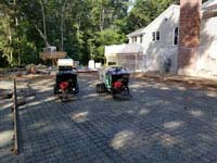 Pouring cement underlay for graphite and orange residential basketball court replacing a dead pool in Walpole, MA.