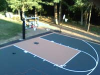 Focus on hoop system and key at one end of large Walpole, MA basketball court on blacktop underlay.
