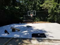 Concrete base is ready to lay low impact tile for black and grey home backyard basketball court in Wellesley, MA.