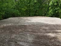 Packed sand and gravel is ready for concrete foundation of black and grey home backyard basketball court in Wellesley, MA.