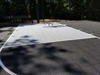 Black and grey home backyard basketball court in Wellesley, MA.