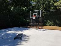 Durable concrete base is ready for low impact tile installation for black and grey home backyard basketball court in Wellesley, MA.
