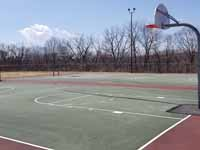 Resurfaced municipal basketball courts in Walpole, NH to create a combo of pickleball and basketball on comfortable, durable royal blue and graphite versacourt tile. This shows part of the old court that was replaced.