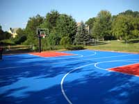 Blue and orange commercial sized backyard basketball court on asphalt base in Bellingham, Massachusetts.