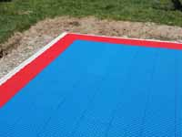 Close-up of a corner of blue and red backyard basketball court in Beverly, MA.