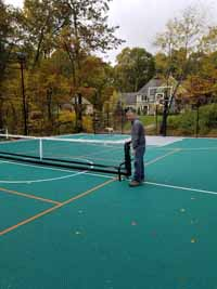 Demonstrating deployment of portable yet durable net system to center of large basketball multicourt in Bolton, MA. Court was ordered with lined for pickleball. Portable nets roll easily then lock down, giving option of net sports like tennis on demand without permanent posts or nets. Shown here in final position.