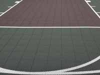 Home basketball court in subdued slate green and burgundy on asphalt in Connecticut.