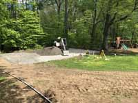 Home basketball court in subdued slate green and burgundy on asphalt in Connecticut. Shown here putting in an underlay that includes packed, crushed stone to make the asphalt under the court more durable.