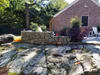 This shows the stone wall and patio area, plus part of the yard where the court will go, prior to Chestnut Hill, MA transformation of a tight backyard space into a slate green basketball court with custom containment net fencing atop wooden fence.
