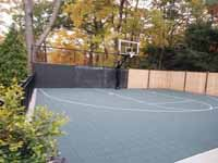 Chestnut Hill, MA transformation of a tight backyard space into a slate green basketball court with custom containment net fencing atop wooden fence.