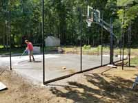 Small residential basketball court in Cranston, Rhode Island, featuring emerald green and sand tiles, and a custom Celtics logo. Shown here, washing dirt off the concrete base before installation of court surface, after fence posts and goal system are in place.