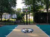 Small residential basketball court in Cranston, Rhode Island, featuring emerald green and sand tiles, and a custom Celtics logo