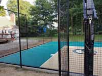 Small residential basketball court in Cranston, Rhode Island, featuring emerald green and sand tiles, and a custom Celtics logo.