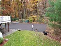 Olive green and grey basketball court with hoop and fencing in Hopkinton, MA. Packing powdered stone as final underlay layer for concrete base.