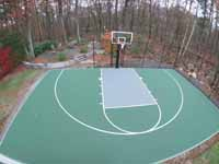 Olive green and grey basketball court with hoop and fencing in Hopkinton, MA.