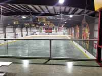 We traveled to Kapolei, Hawaii and inside to resurface two inline skate hockey rinks with Versacourt Speed Indoor tile. This is a photo from the elevated bleacher area at one end, through the safety netting, before the work began.