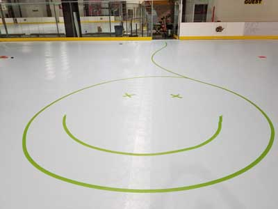 We traveled to Kapolei, Hawaii and inside to resurface two inline skate hockey rinks with Versacourt Speed Indoor tile. This is a happy face picture taped onto the first of those courts.